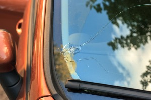 A large crack in the side of a windshield, requiring Windshield Replacement in Macomb IL