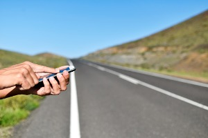 Man calling someone on his cellphone, stranded on the side of the road